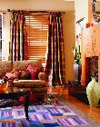 Colorfull casual draperies puddled to floor over wooden horizontal blinds -- Jupiter Florida Home